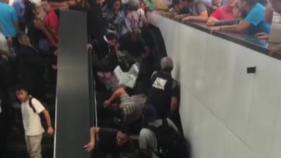 Des personnes prennent l'escalator alors qu'il n'y a plus de place à la sortie
