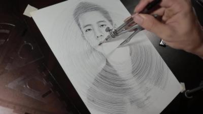 Il dessine un portrait en utilisant qu'un compas