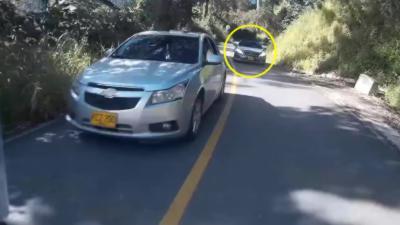 Une voiture double dans un virage et percute un motard