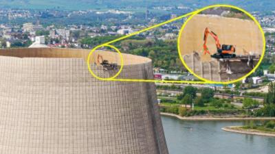 Une pelleteuse perchée à 180 mètres de hauteur sur le sommet d'une tour de refroidissement