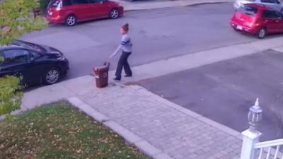 Une femme qui marche dans la rue balance violemment une poubelle sur une voiture