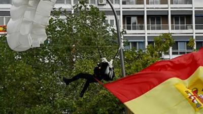 Un parachutiste se coince dans un lampadaire pendant un défilé militaire