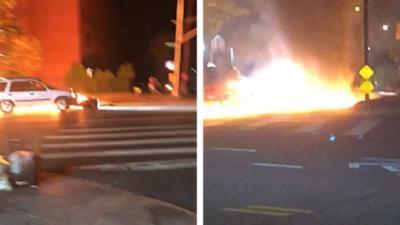 Une voiture pousse une moto en feu sur la route
