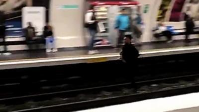Un parisien court sur la voie du métro pendant qu'il se fait courser par un contrôleur