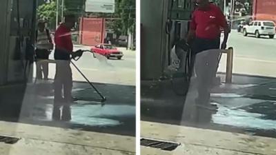 Il nettoie le sol de la station service avec une pompe à essence