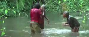Une femme et ses enfants jouent de la musique avec l'eau d'une rivière